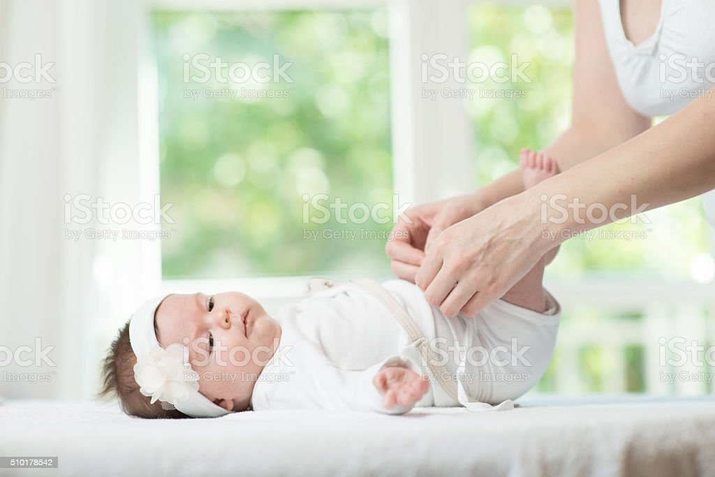 Mother changes her babies nappy stock photo