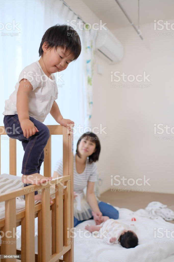 mother changing diaper of baby and playing toddler - Royalty-free 0-1 Months Stock Photo