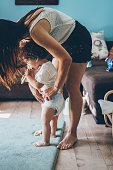 Mother changing diaper on toddler while standing