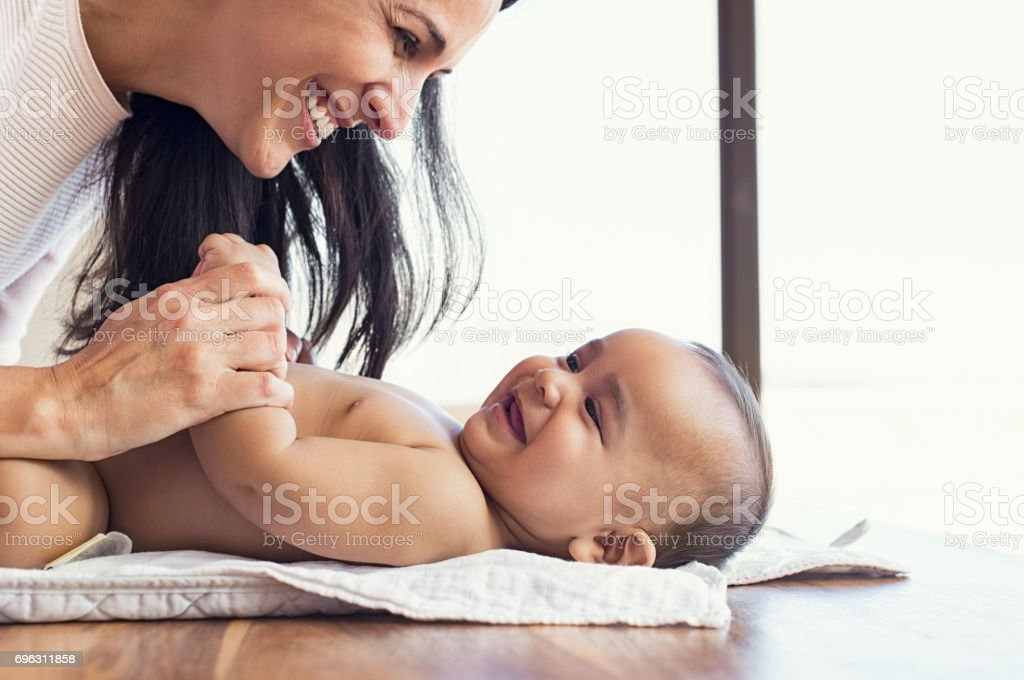 Mother changing diaper to toddler