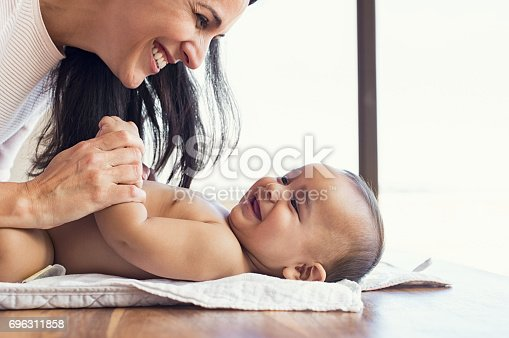 istock Mother changing diaper to toddler 696311858