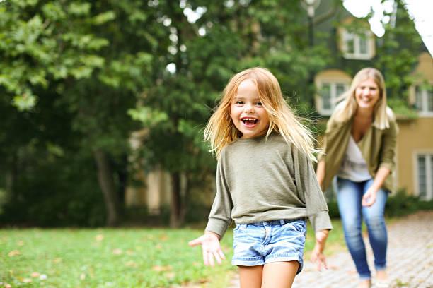 mother chasing girl outdoor. - mutter kind heim stock-fotos und bilder