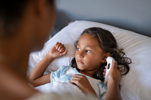 Close up of african mom using ear thermometer to check temperature of little sick girl lying on bed. Ill indian daughter resting in bed while woman checking fever. Portrait of girl with cold and flu symptoms while mother sitting next to hear.