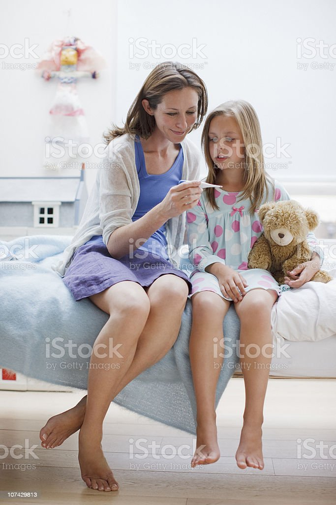 Mother checking daughters temperature with digital thermometer stock photo
