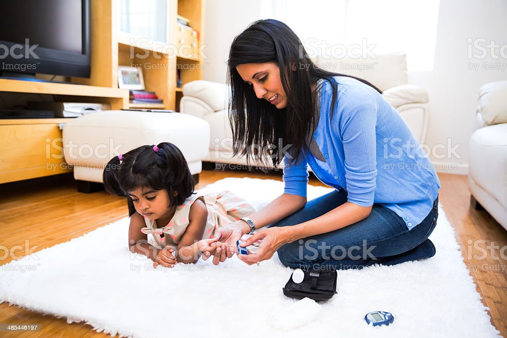 Mother checking her daughters' diabetes by monitoring blood  glucose level stock photo