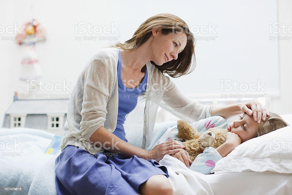 Madre controllando sul male figlia sdraiati a letto - foto stock