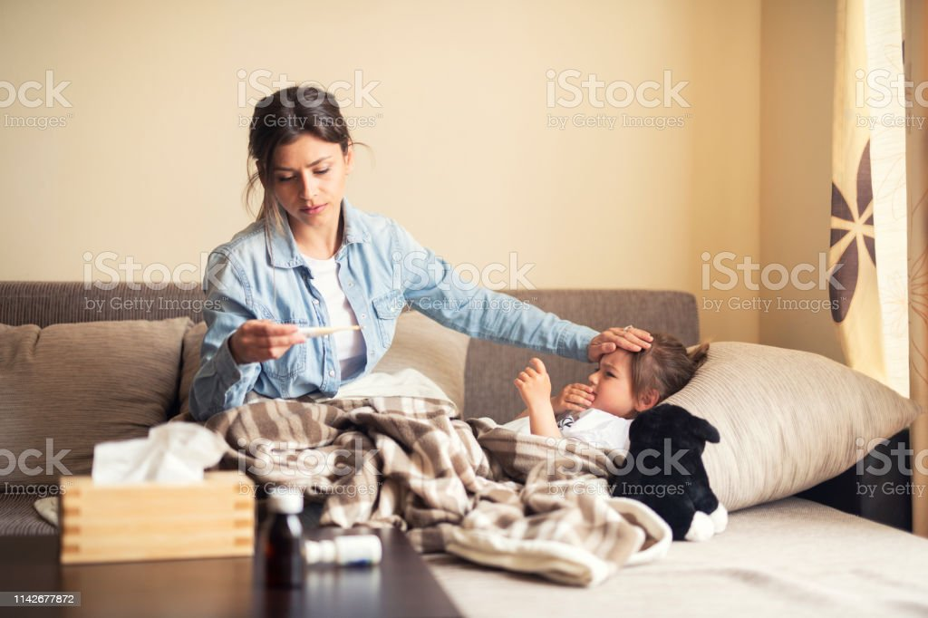 Mother checking on sick daughter laying in bed - Royalty-free 2-3 Years Stock Photo