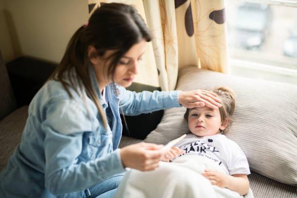 мать проверяет больную дочь, лежащей в постели - болезнь стоковые фото и изображения