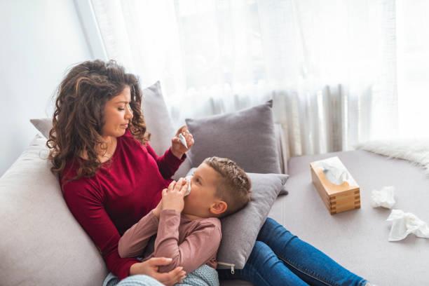 madre che controlla la temperatura di suo figlio malato. - china drug foto e immagini stock