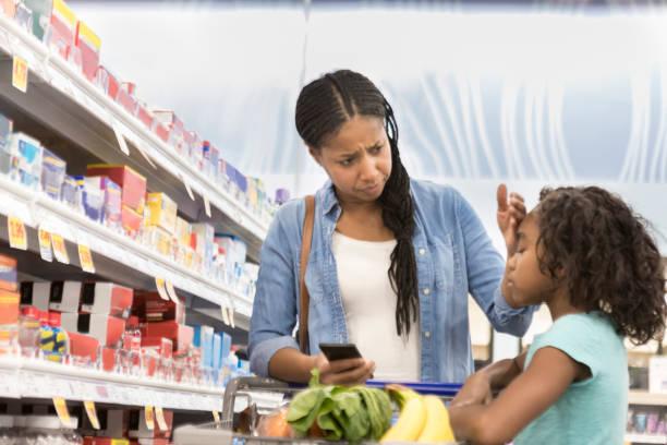 Mother checks daughter for fever in supermarket pharmacy stock photo