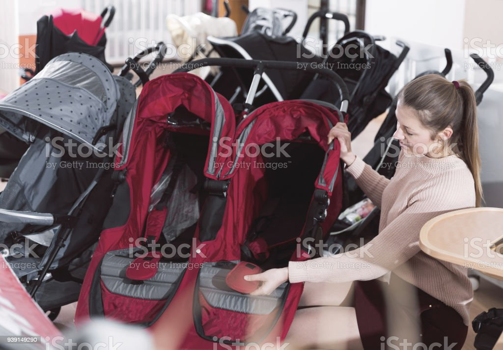 Mother choosing twins stroller stock photo