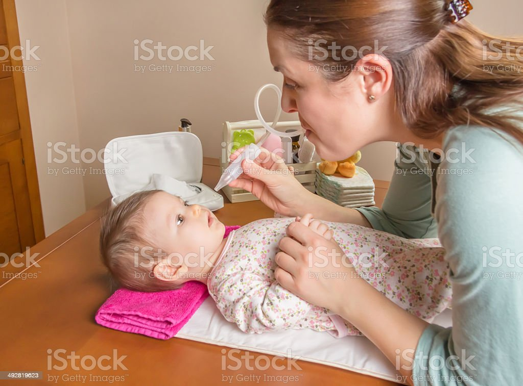 Mother cleaning mucus of baby with nasal aspirator stock photo