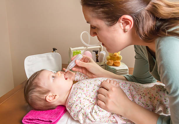 Mother cleaning mucus of baby with nasal aspirator Mother cleaning mucus catarrh of adorable baby with a nasal aspirator mucus stock pictures, royalty-free photos & images