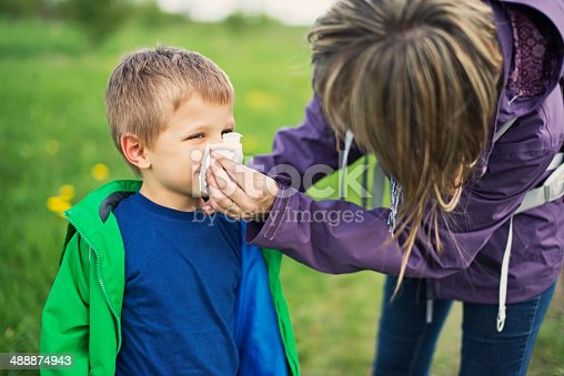 629307146istockphoto Mother cleaning nose of sick son 488874943