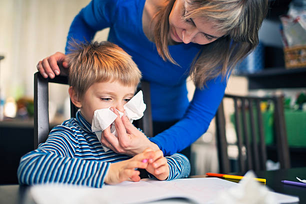 Mother cleaning nose of sick son stock photo