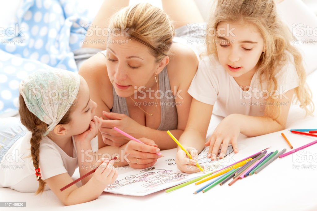 Mother Coloring With Her Children stock photo