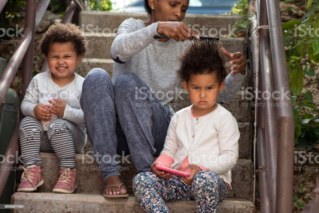 Mother combing daughter's afro hair. stock photo