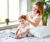 cute mother combing hair daughter in bed