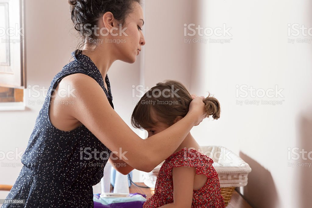 Mother combing the hair of her daughter stock photo