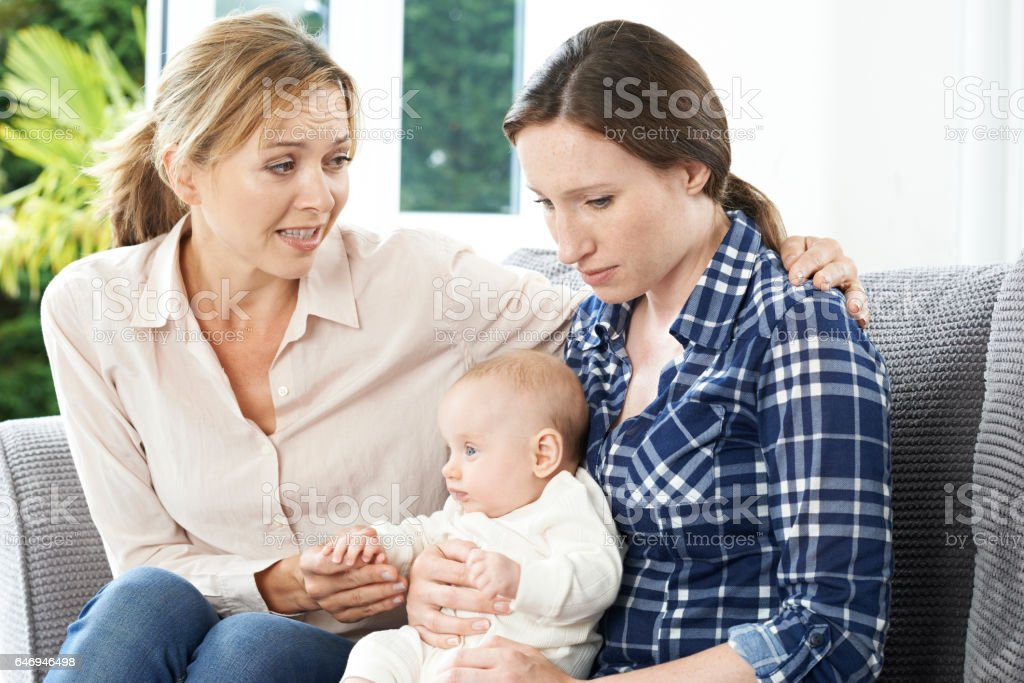 Mother Comforting Adult Daughter Suffering With Post Natal Depression stock photo