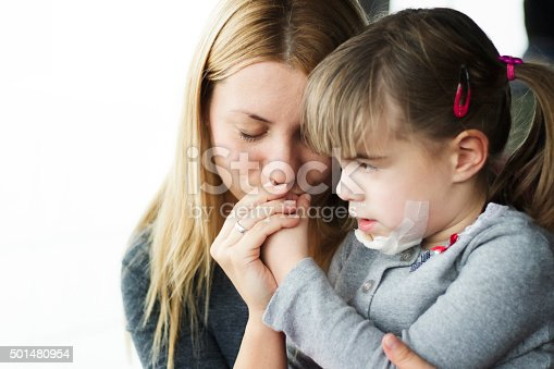 istock Mother comforting child with injured and bandaged chin 501480954