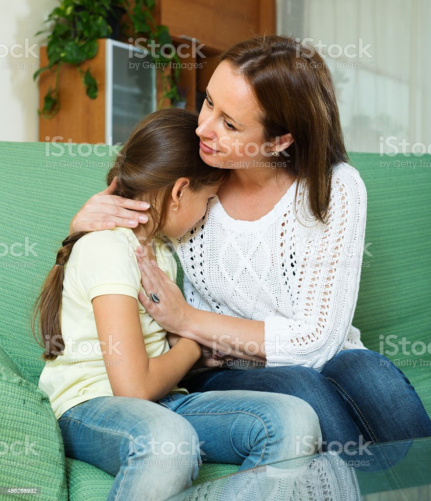 Mother comforting crying  daughter stock photo