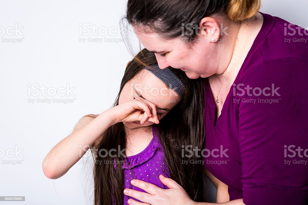 mother comforting her daughter stock photo