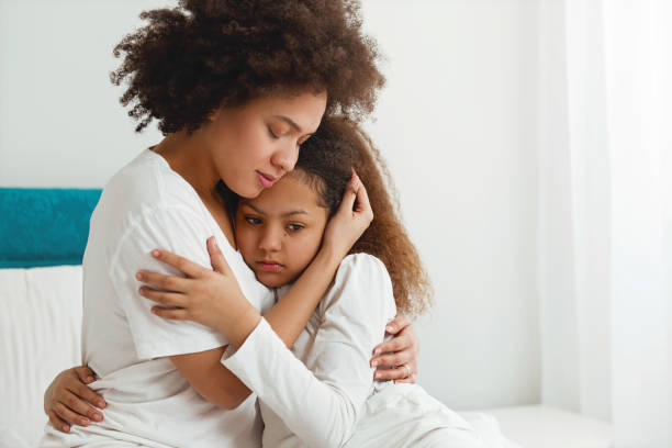 Mother comforting her daughter, sitting in the bedroom, hugging stock photo