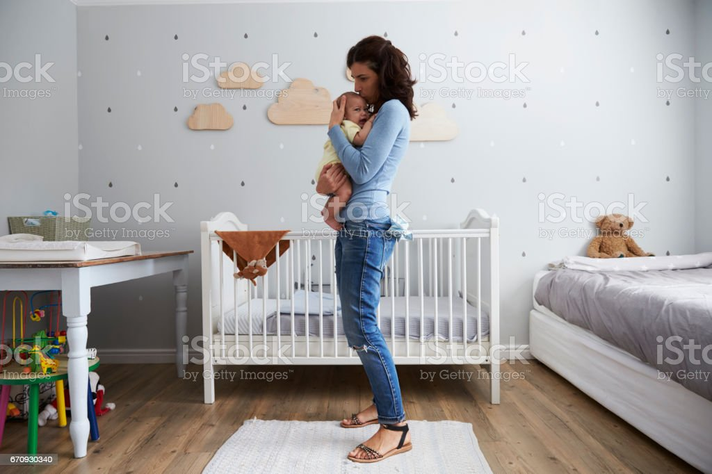 Mother Comforting Newborn Baby Son In Nursery stock photo