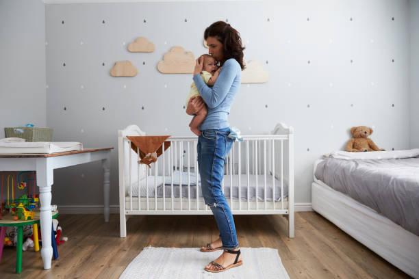 Mutter tröstet neugeborenen Sohn im Kindergarten – Foto