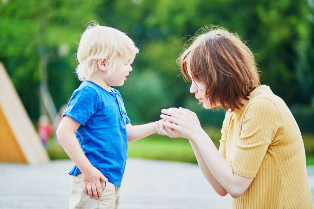 Mother comforting son after he injured his hand stock photo