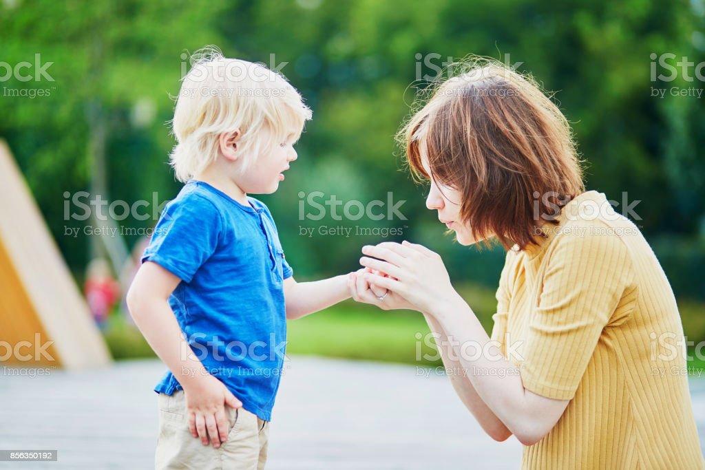 Mère fils réconfortant après avoir blessé sa main - Photo