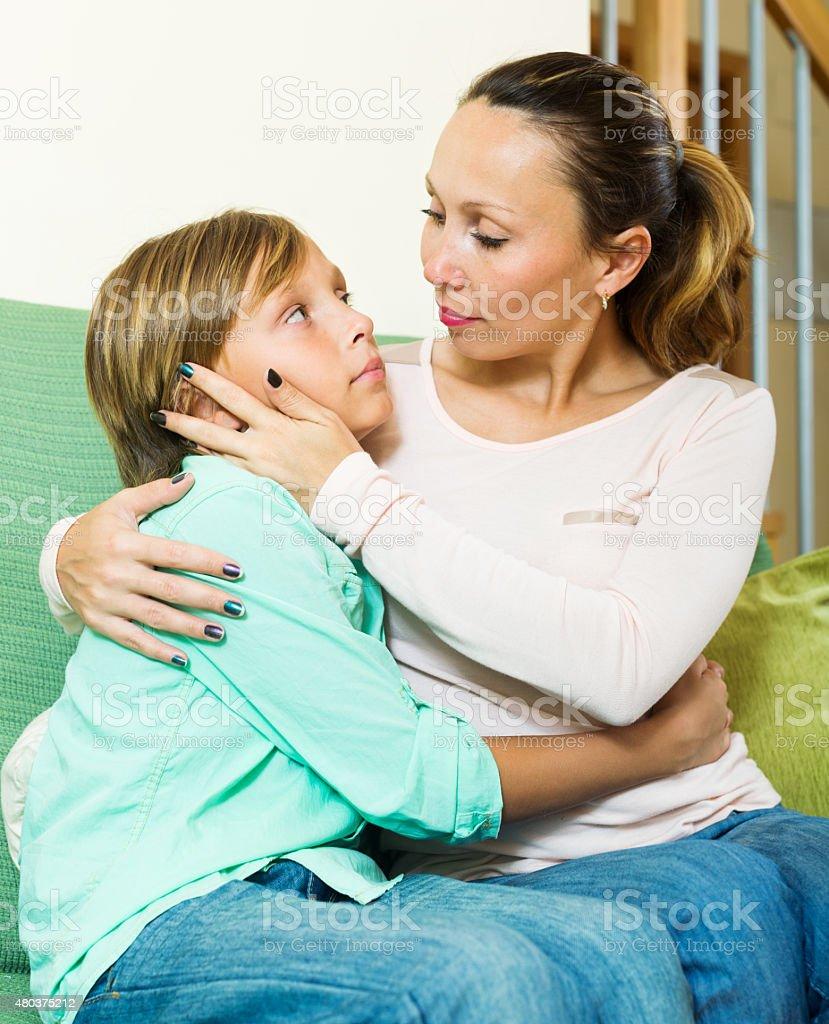 mother comforting teenage boy stock photo