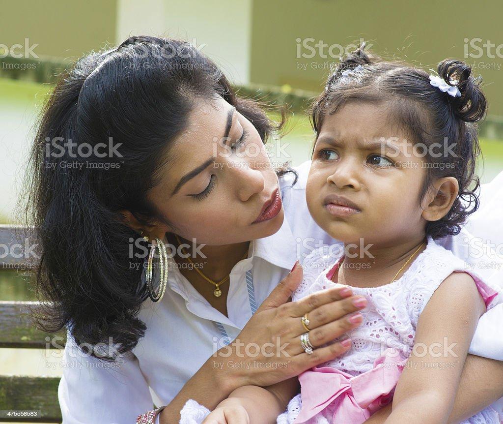 Mother comforting upset Indian girl stock photo