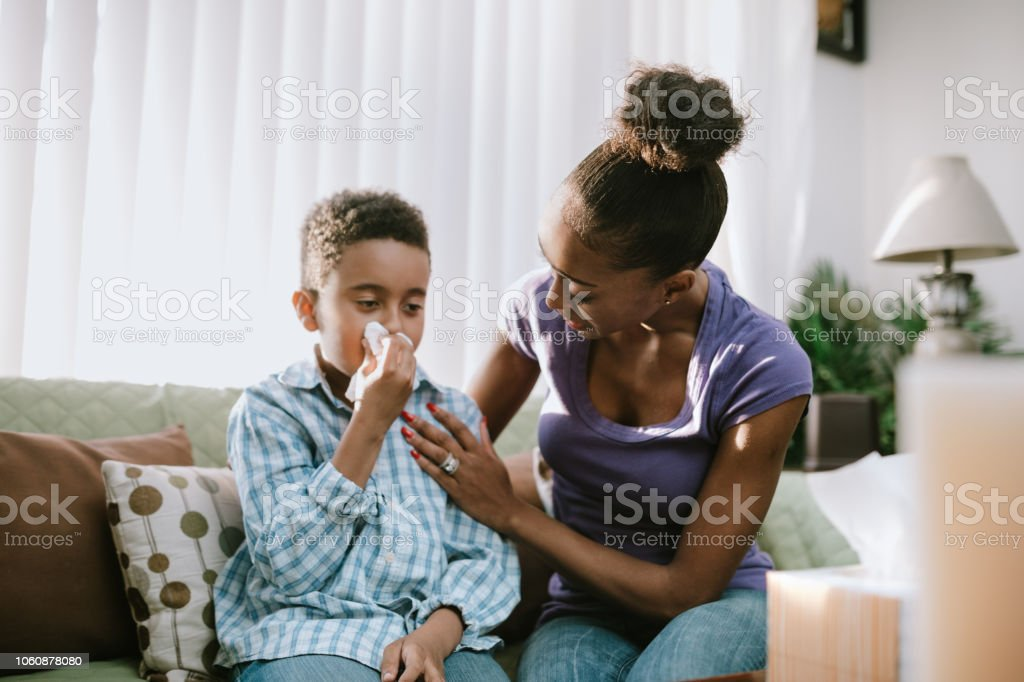 Mother Comforts Sick Child With Cold stock photo