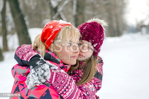 Portrait of mother and daughter together outdoor on winter cold day,parent care for pre adolescent child feelings