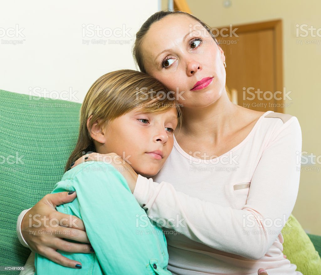 mother consoling crying teenage son at home stock photo