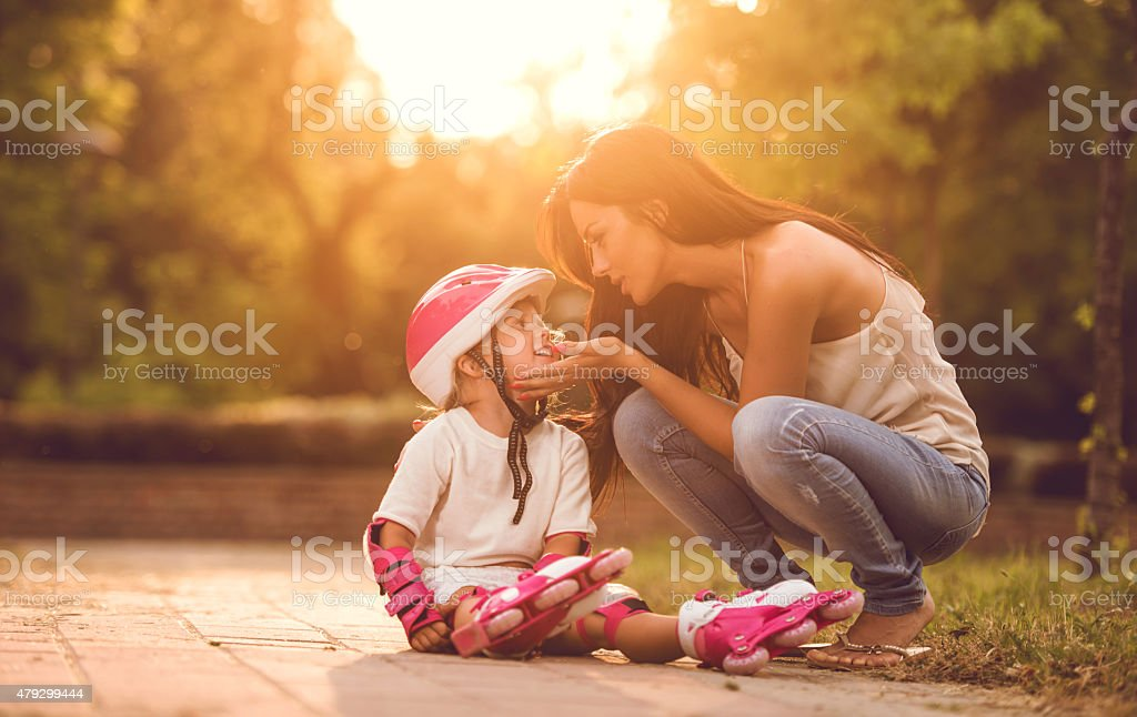 Mother consoling her daughter who fell while driving rollerblade. stock photo