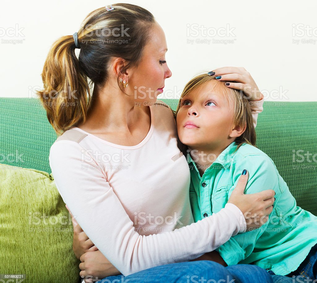 Mother consoling sad teenager at home stock photo