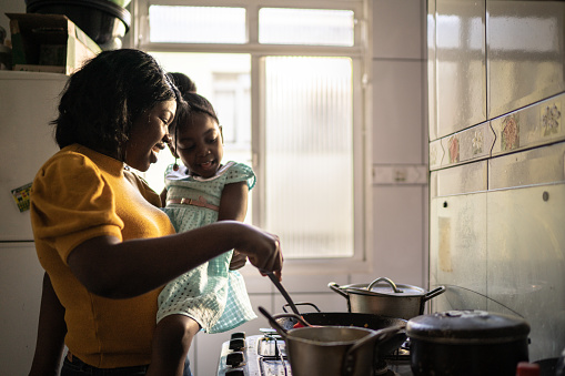 Mother cooking at home while holding her daughter