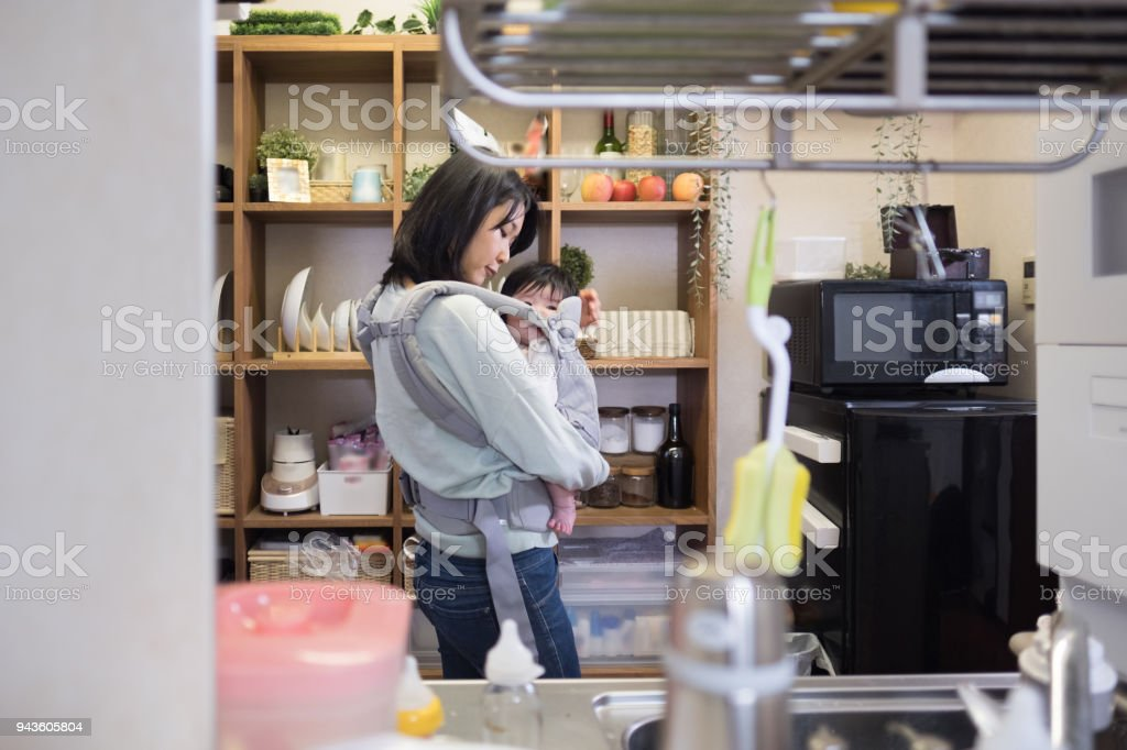 赤ちゃんとの台所で調理の母 ストックフォト