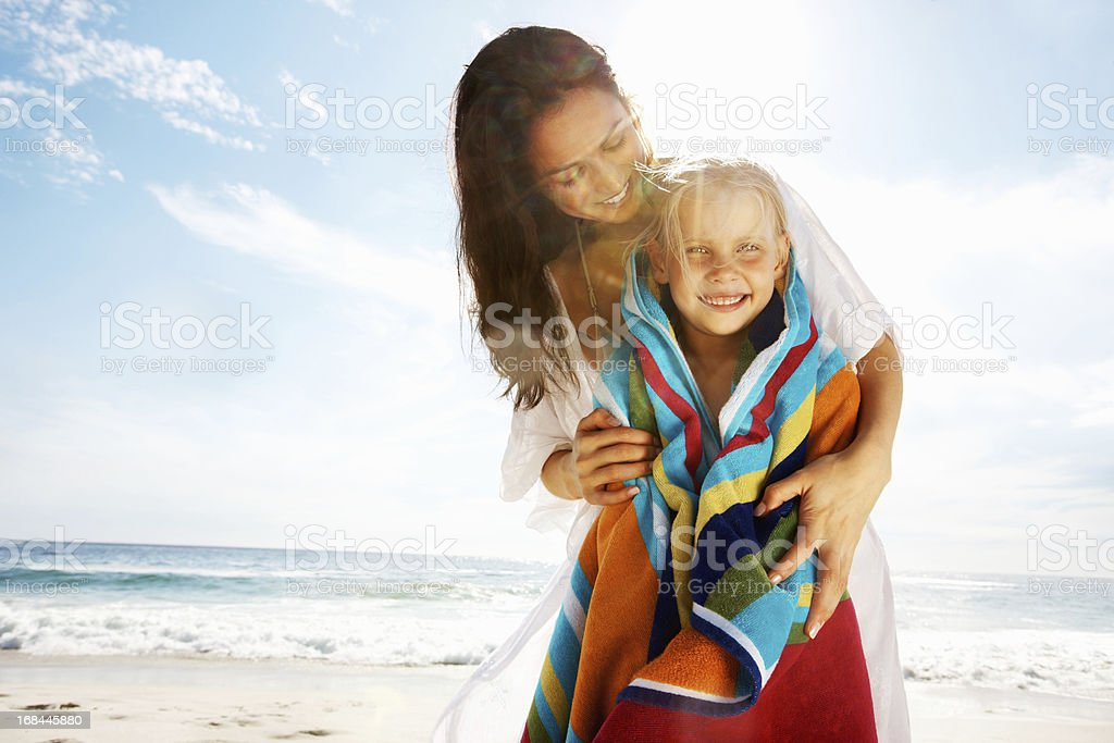 Mother covering daughter with towel on the beach royalty-free stock photo