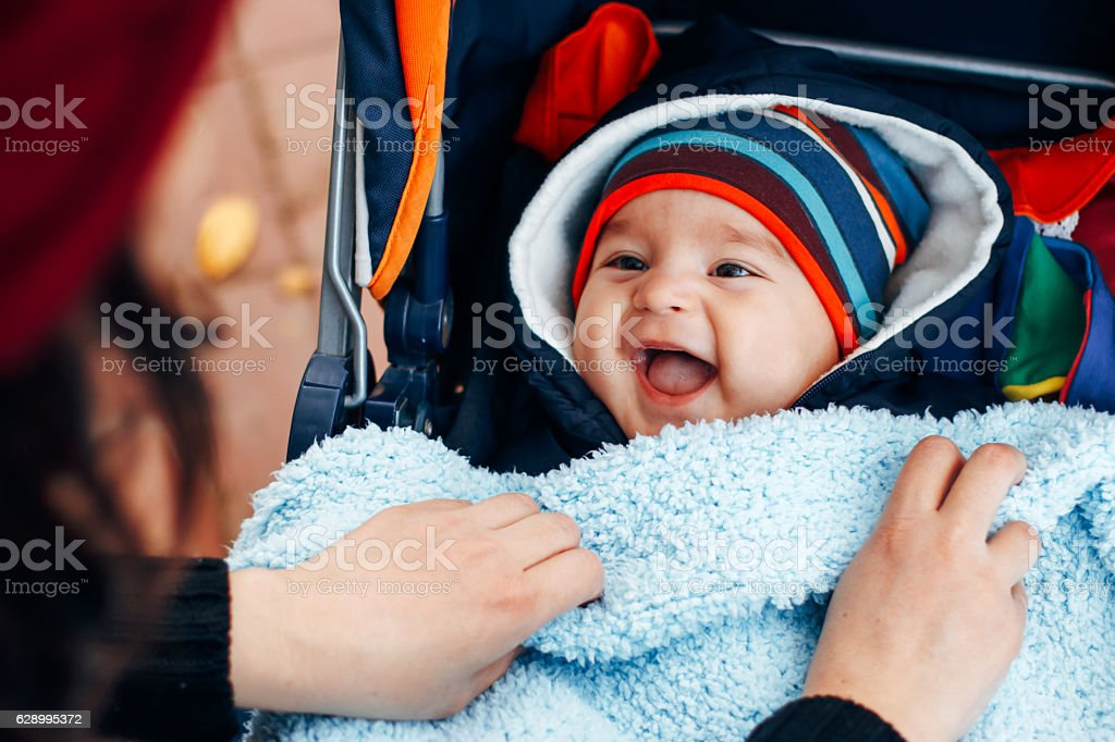 Mother covers son with blankets stock photo