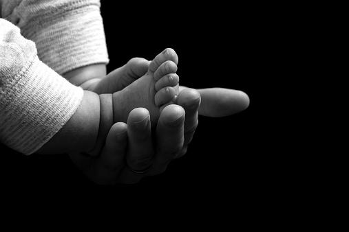 istock Mother cradling the feet of her newborn baby 523510135