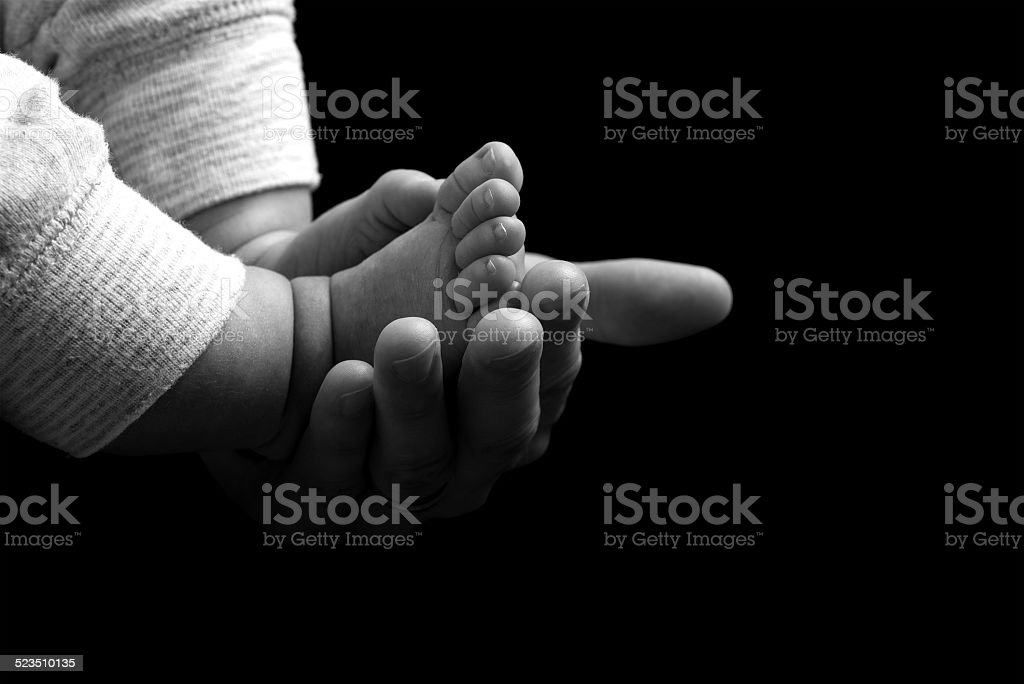 Mother cradling the feet of her newborn baby stock photo