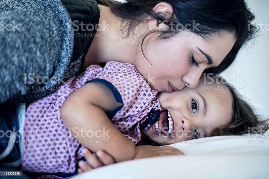 Mother cuddling and kissing her son stock photo