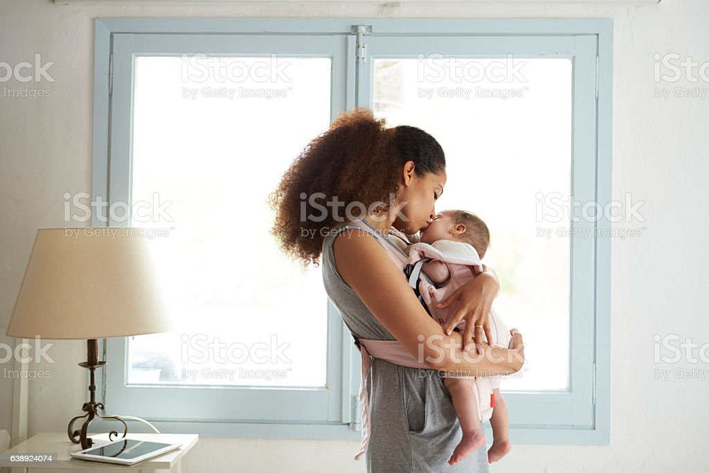 Mother Cuddling Baby Daughter At Home In Front Of Window stock photo