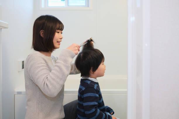 mutter des kindes schneiden haare im bad - kleinkind frisur stock-fotos und bilder