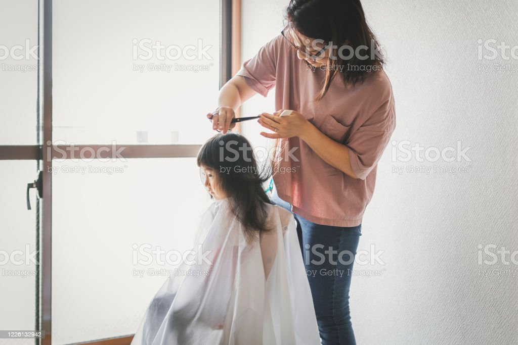 Mother cutting her daughter's hair at home Asian mother doing haircut in the living room. Affectionate Stock Photo