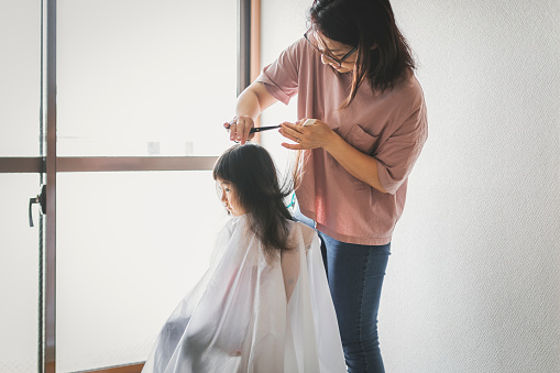 Mother Cutting Her Daughters Hair At Home Stock Photo - Download Image Now
